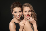 Beautiful young women with elegant jewelry on dark background - 209849508