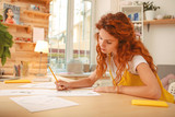 Working table. Red-haired appealing fashion designer working very hard with sketches while sitting at the wooden working table - 209849563