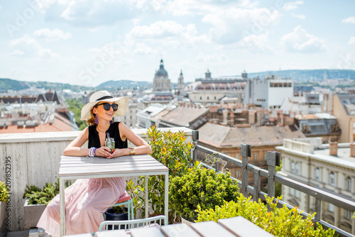 Woman enjoying great cityscape view from the terrace on the old town with saint Stephen cathedral in Budapest city, Hungary © rh2010