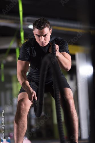 lekkoatleta mężczyzna robi liny bitwy krzyż fitness ćwiczenia