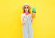 Leinwanddruck Bild - Fashion pretty woman with a pineapple, cup of juice in white striped pants, round hat on yellow background