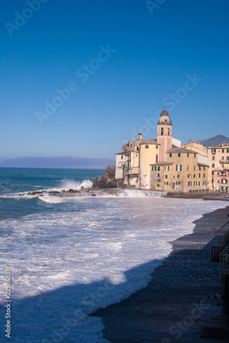 Fotobehang Liguria Church of Camogli in a day with sea storm that overwhelms beach and pier - Genoa