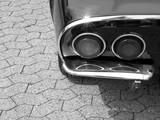 Runde Rückleuchten mit Chromring einer deutschen Sportwagenlegende der späten Sechzigerjahre auf grauem Verbundpflaster in Lage im Kreis Lippe, fotografiert in klassischem Schwarzweiß