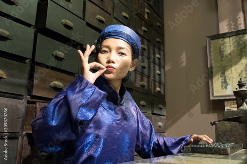 Fotobehang Apotheek Asian pharmacist working at oriental pharmacy from the 19th century. Woman in traditional costume eastern druggist in the ancient drug store.
