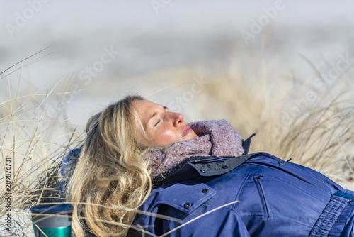 Foto Murales Schöne Frau liegt in der Sonne auf einer Düne und schläft