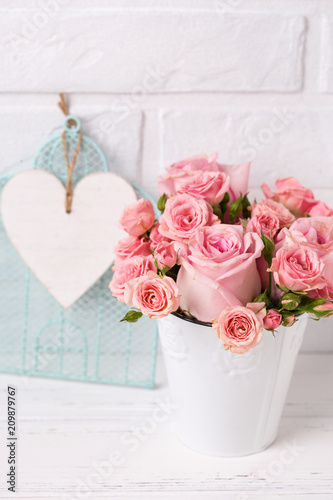 Wall mural Pink roses flowers  in white pot  against  white brick wall.