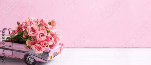 Retro car toy with pink roses flowers against pink textured wall. Long bannerformat.