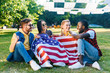multiracial smiling friends with american flag sitting on green grass in park