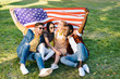 multiracial cheerful friends with american flag sitting on green grass in park