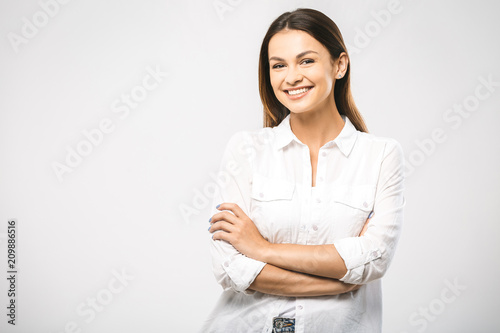 Foto Murales Portrait of happy smiling young beautiful woman, isolated over white background. Looking at camera. Free space for text.