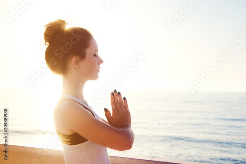 Obraz na płótnie Young woman practicing yoga outdoors by the sea at sunset. Girl standing with eyes closed and prayer hands. Female portrait in profile.