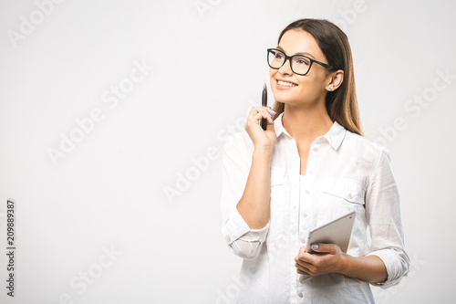 Fototapeta Young beautiful smiling woman in glasses holding pen, isolated on white. Business concept with laptop. Place for text.