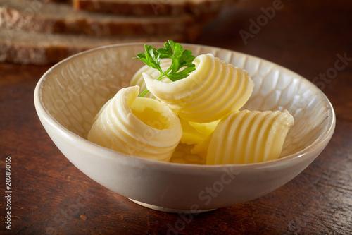 Leinwanddruck Bild Close up Cute little bowl of fresh butter curls