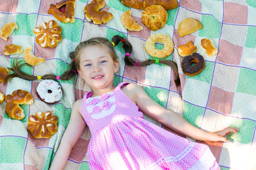 The girl lies on a plaid among the products of bread. Around the head of a beautiful girl laid out a lot of bread and baking.