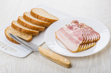 Slices of bacon in plate, bread on cutting board, knife