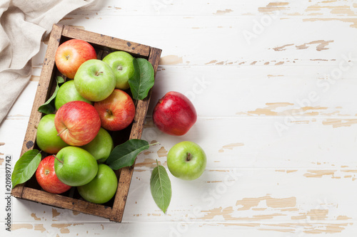 Green and red apples in wooden box - 209897742