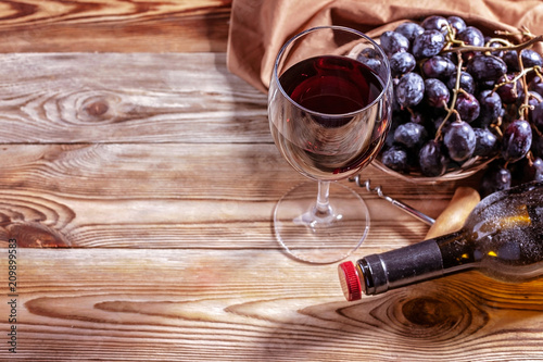Foto Murales Red wine. Red wine in a glass, red grapes and dusty bottle on a wooden background. Copy space