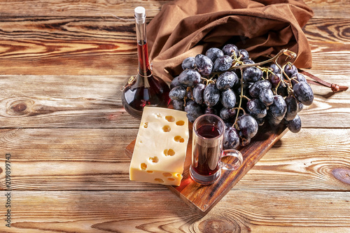 Foto Murales Red wine, cheese and red grapes on a wooden background. Top view