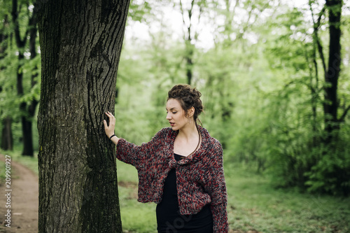 Young woman in the park by tree
