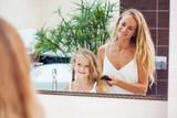 Mother combing daughter hair
