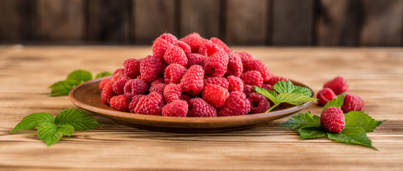Tasty juicy sweet raspberry on a wooden background. It can be used as a background © chernikovatv