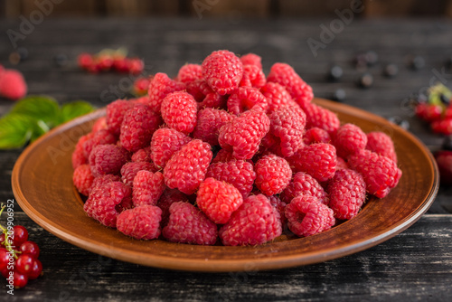 Tasty juicy sweet raspberry on a wooden background. It can be used as a background