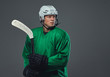 Hockey player wearing green protective gear and white helmet standing with the hockey stick. Isolated on a gray background.