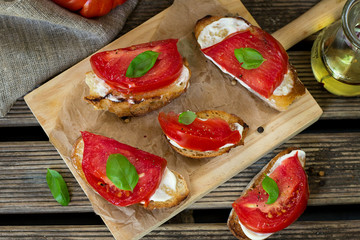 Grilled bread topped with mayonnaise, tomato and basil leaf
