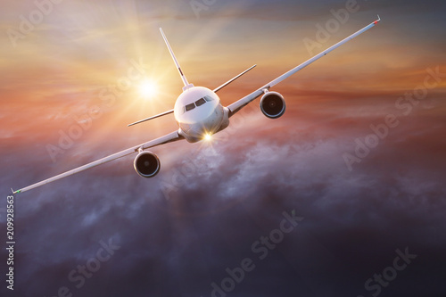 Foto Murales Commercial airplane flying above clouds.