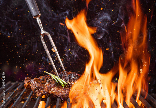 Beef steak on the grill with flames - 209928590