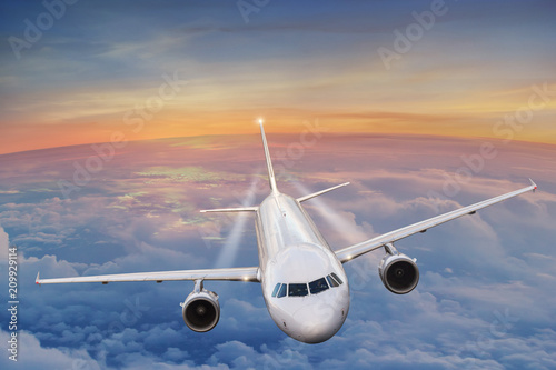 Leinwanddruck Bild Commercial airplane flying above clouds.