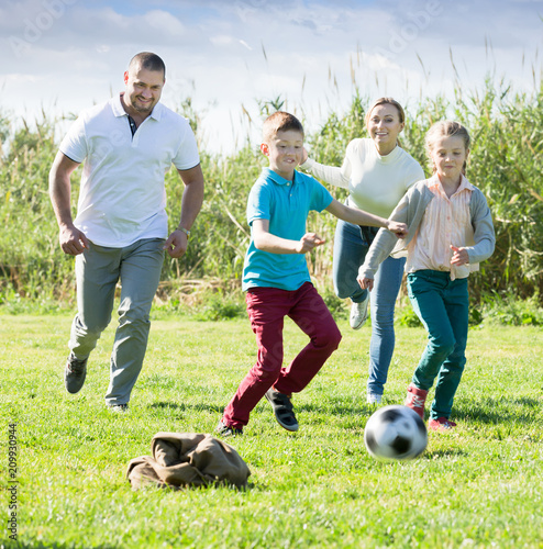 Foto Murales Cheerful parents with two kids playing soccer