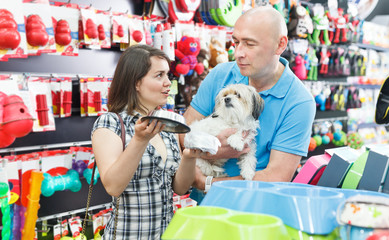 Couple purchasing pet bowls in pet shop