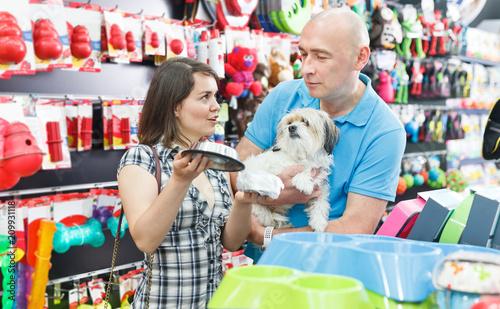 Couple purchasing pet bowls in pet shop - 209931118