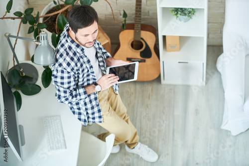 Fototapeta From above shot of casual man holding tablet and leaning on table in modern office studio looking away in inspiration.