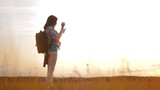 Hipster hiker silhouette girl is shooting video of beautiful nature sundown on cell telephone smartphone slow motion video. Female tourist is lifestyle taking photo with mobile phone camera. female - 209965110