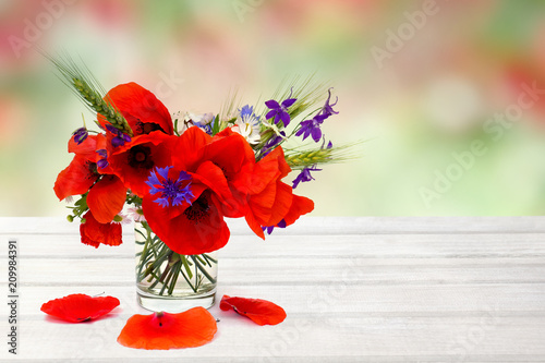 Leinwanddruck Bild Red poppies, cornflowers, ears of green wheat, chamomile in small vase on white wooden table on summer blur natural background with space for text.