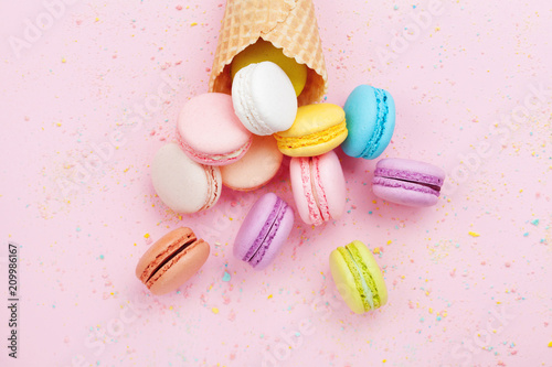 Sweet waffle cone with macaron or macaroon on pink pastel background top view. Flat lay composition.
