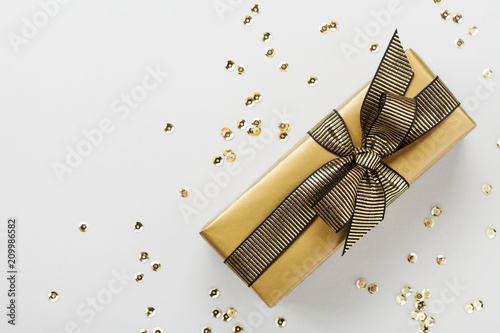 Gift or present box and golden sequins on table top view. Flat lay composition for Christmas or birthday.