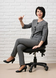 the business woman sitting on a chair, dressed in a gray suit poses in front of a white wall - 209986720