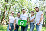 young happy volunteers with green recycling box in park - 209988339