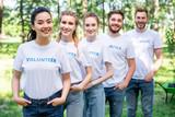 young smiling volunteers standing in row in park - 209992570