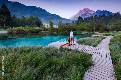 Plakat Active man with dog watching sunrise in Zelenci Park, Slovenia