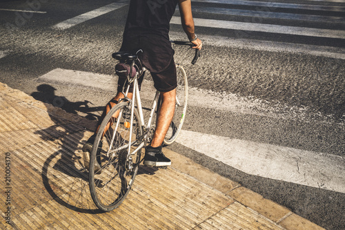 Plexiglas Fiets Man crossing a crosswalk with his old road bike, wearing casual clothes.