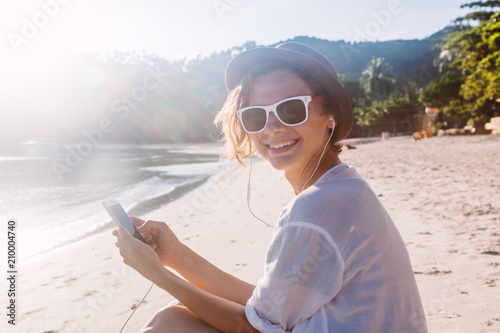 Young beautiful woman hipster traveler in headphones and with mobile phone in hands, on the beach in the sun
