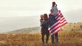 happy family with flag of america USA at sunset outdoors - 210005715