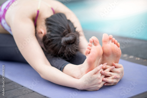 Leinwanddruck Bild Young Asian attractive woman doing yoga exercise near swimming pool. Pilates workout and healthy lifestyle concepts. International yoga day