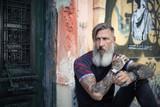 Porträt eines attraktiven, bärtigen, tätowierten Mannes, der in der Stadt vor einer Tür sitzt