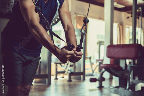 Fotobehang Fitness Unrecognizable muscular man in sportswear wrapped up in doing exercise while having workout at spacious gym
