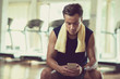 Handsome young sportsman texting with friend on smartphone and sitting on bench of modern gym while taking short break from intensive training